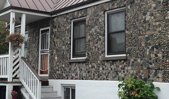 "Detail of the Hamel Stone house. Built in 1945. Note the ""cut stone"" blocks alternating with the ""round pebble"" blocks."